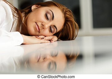 Young businesswoman fallen asleep at office table