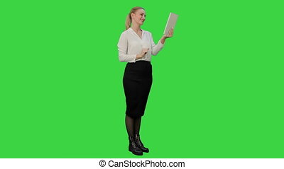 Young businesswoman have a video chat on tablet computer on a Green Screen, Chroma Key.