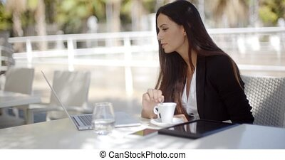 Young businesswoman having a coffee break sitting at an open...