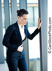 young businesswoman having period pain in office