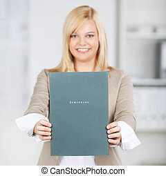 Young Businesswoman Holding Application File In Office