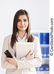 Young businesswoman holding digital tablet and mobile phone
