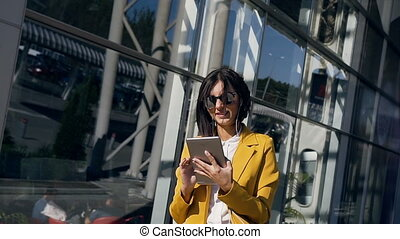 Young businesswoman in a suit is working on tablet computer near modern glass business centre during a lunch break. Concept of business, technology and people