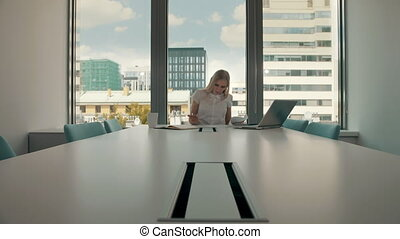 Young businesswoman in conference room with papers. Elegant blond woman sitting at long table in modern hall of office with laptop and writing on papers while working.