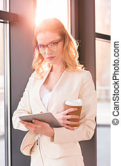 young businesswoman in glasses standing and holding digital tablet and coffee cup