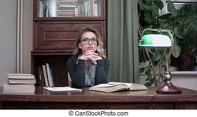 Young businesswoman in glasses thinking over her project and suddenly having a genius idea