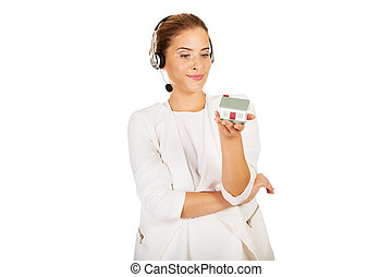 Young businesswoman in headset holds house model