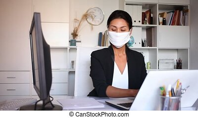 Young businesswoman in medical mask working with laptop and papers in office. High quality FullHD footage