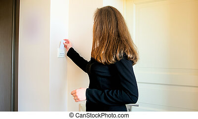 Young businesswoman inserting key card in electric swith at hotel room