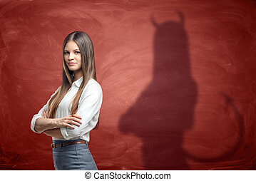 Young businesswoman is casting shadow of devil on rusty...