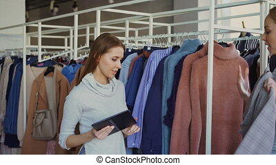 Young businesswoman is using tablet while checking goods in her clothing store. Assistant is coming with garment and asking advice. Business owner is giving orders.