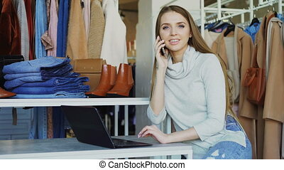 Young businesswoman is working with laptop and talking on...