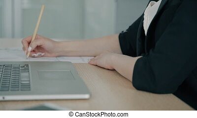 Young businesswoman is writing, sitting at desk with laptop in modern office.