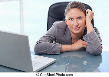 Young businesswoman leaning on her desk