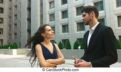 Young businesswoman listening to her manager on the street. Close up of big modern business center.
