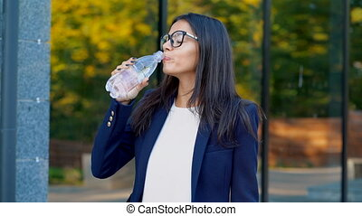 Young businesswoman near office building drinks mineral...