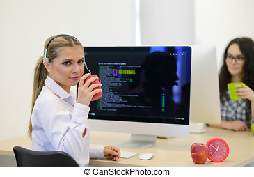 Young businesswoman on a coffee break. Using computer.