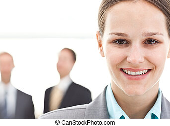 Young businesswoman posing in front of two businessmen