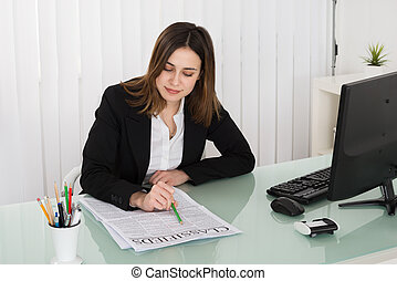 Businesswoman Reading Classifieds On Newspaper
