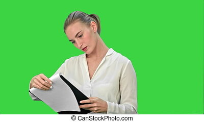 Young businesswoman reading documents on a Green Screen, Chroma Key.