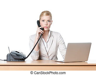 Young businesswoman sitting at a office table and holding phone handset, isolated