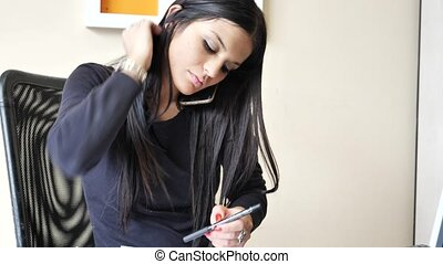 Young businesswoman sitting at desk in office busy on phone