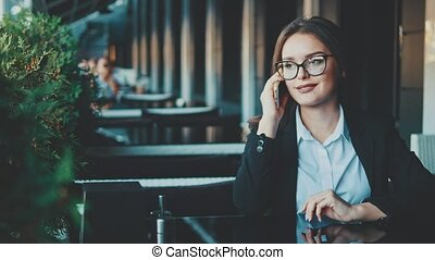 Young businesswoman sitting in a cafe decides some business.