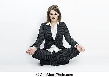 Young businesswoman sitting in lotus position.