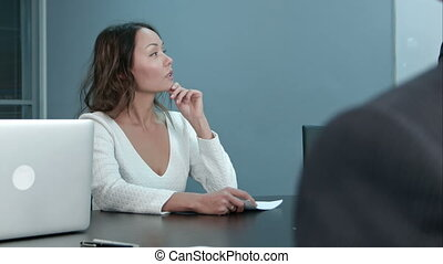 Young businesswoman sitting on business meeting with colleagues in office, asking questions