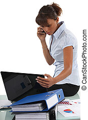 young businesswoman sitting on her desk and looking at her laptop