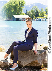 Young Businesswoman Sitting on Large Rock by Lake