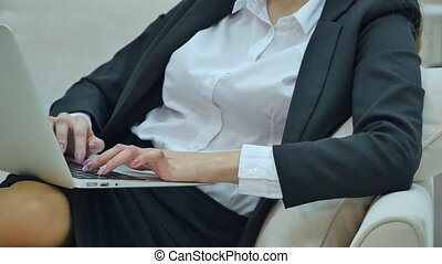 Young businesswoman sitting on sofa, working with laptop computer