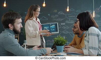 Young businesswoman speaking to colleagues pointing at laptop screen in office