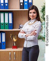 Young businesswoman standing next to shelf