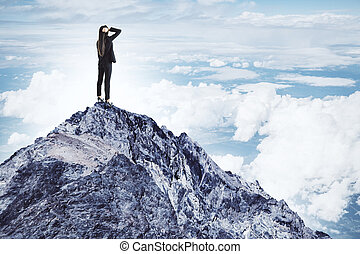 Young businesswoman standing on mountain peak