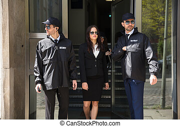 Businesswoman Stepping Out From Office Building