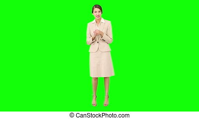Young businesswoman talking at camera on green screen background