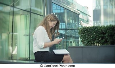 Young businesswoman talking is using smartphone in city park business center