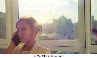 Young businesswoman talking on mobile phone while standing by window in office at sunny day. 1920x1080