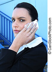 Young businesswoman using a cellphone on a fire escape