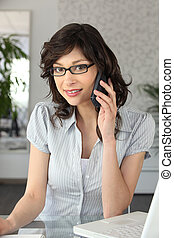 Young businesswoman using a phone and laptop
