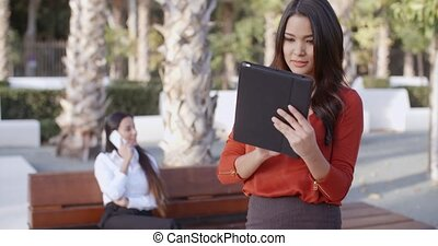 Young businesswoman using a tablet outdoors