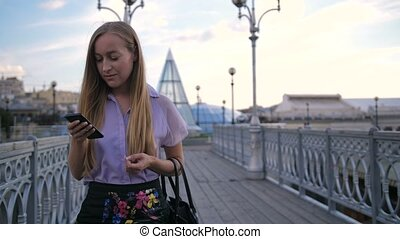 Young businesswoman walking on bridge with phone