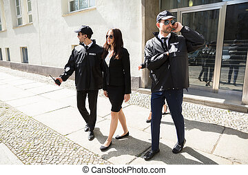 Young Businesswoman Walking On Sidewalk