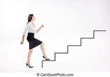 Young businesswoman walking up on stairs - Young ...