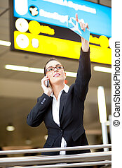 young businesswoman waving to someone while talking on cell...