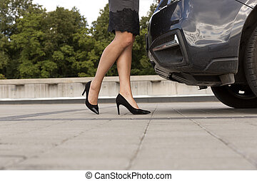 Young businesswoman wearing heels standing next to the car