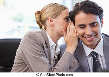 Young businesswoman whispering something to her colleague in...