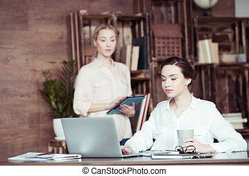 Young businesswoman with digital tablet looking at colleague using laptop