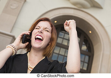 Young Businesswoman with Fist in Air On Cell Phone